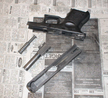 Disassembled Glock parts: (top) slide (bottom row left to right) recoil spring, barrel, slide.