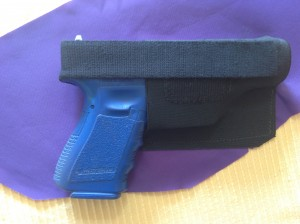 The strap goes over the back of the gun, above the grip so you can easily get your hand on the gun. Stretch the elastic a little to give it some tension.