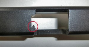 Looking down through the ejection port on a disassembled Glock 26, you can see the extractor -- a small bar or hook in front of the breech face near the firing pin.
